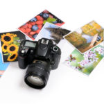 reflex camera with colorful photos on white background