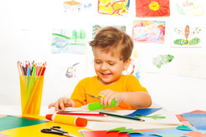 Happy small boy crafting with scissors, paper and glue sitting at the table with drawings on background