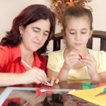 mother and daughter working on an art project at home with some art supplies on the table